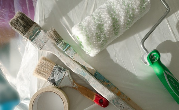 Paint brushes and other supplies for painting a room.