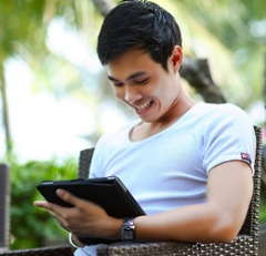 Young man looking at a tablet outside.