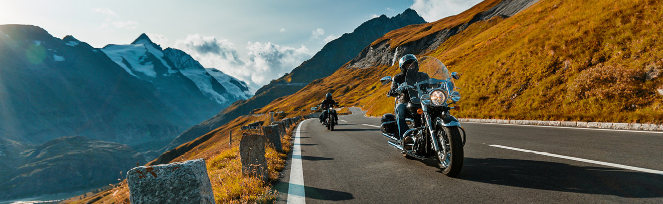 Two people riding motorcycles in the mountains.