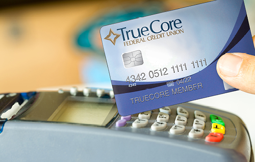 Image of a TrueCore debit card being used at a card scanner.
