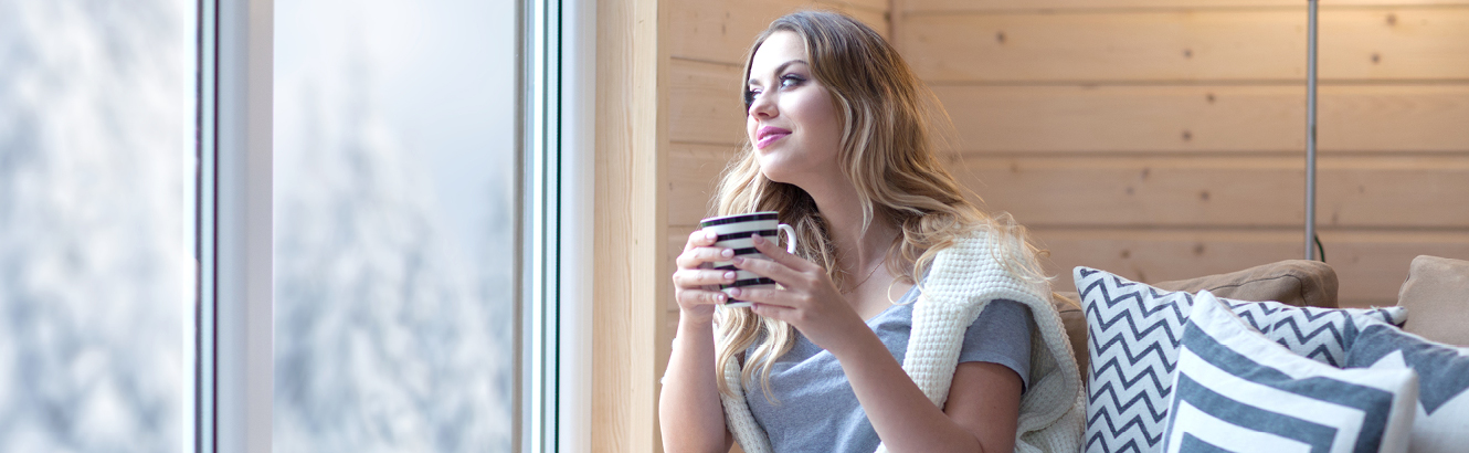 woman drinking coffee at home, gazing out the window